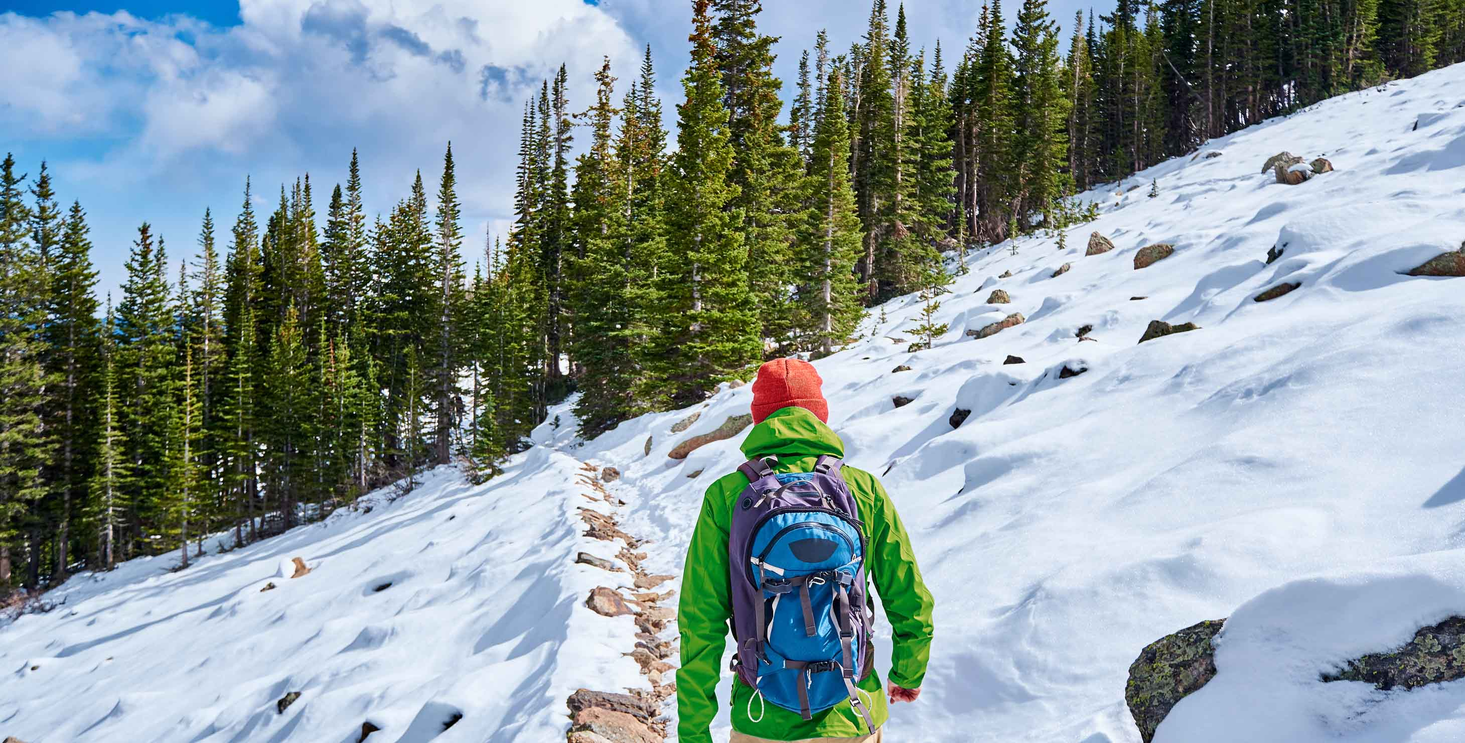 Man hiking on a trail in snow