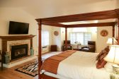 4 poster king size bed in a spacious room with hardwood floors, flat screen tv, and fireplace