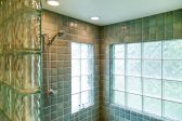 Walk-in shower with green tile and glass block