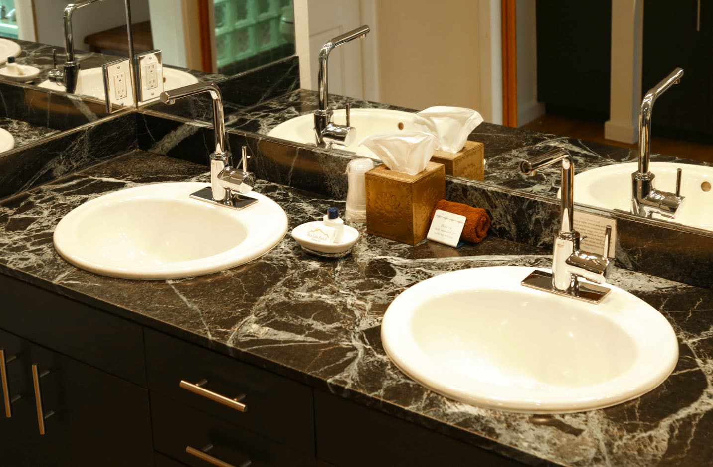 Double vanity sink with a black marble counter top