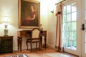 A writing desk with a painting of a portrait of a woman on the wall with double french doors