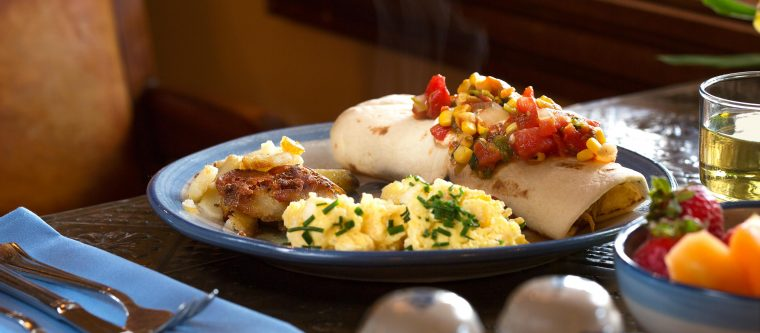 Breakfast burrito topped with corn salsa served with a side of breakfast potatoes and eggs