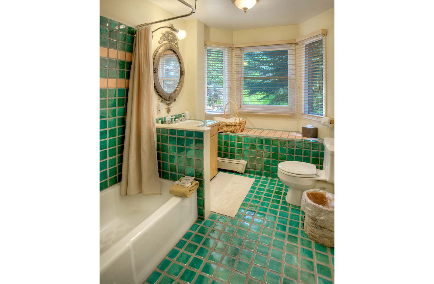 Teal tiled bathroom with bay windows and a shower