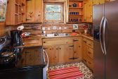 Complete kitchen with large refrigerator and electric stove