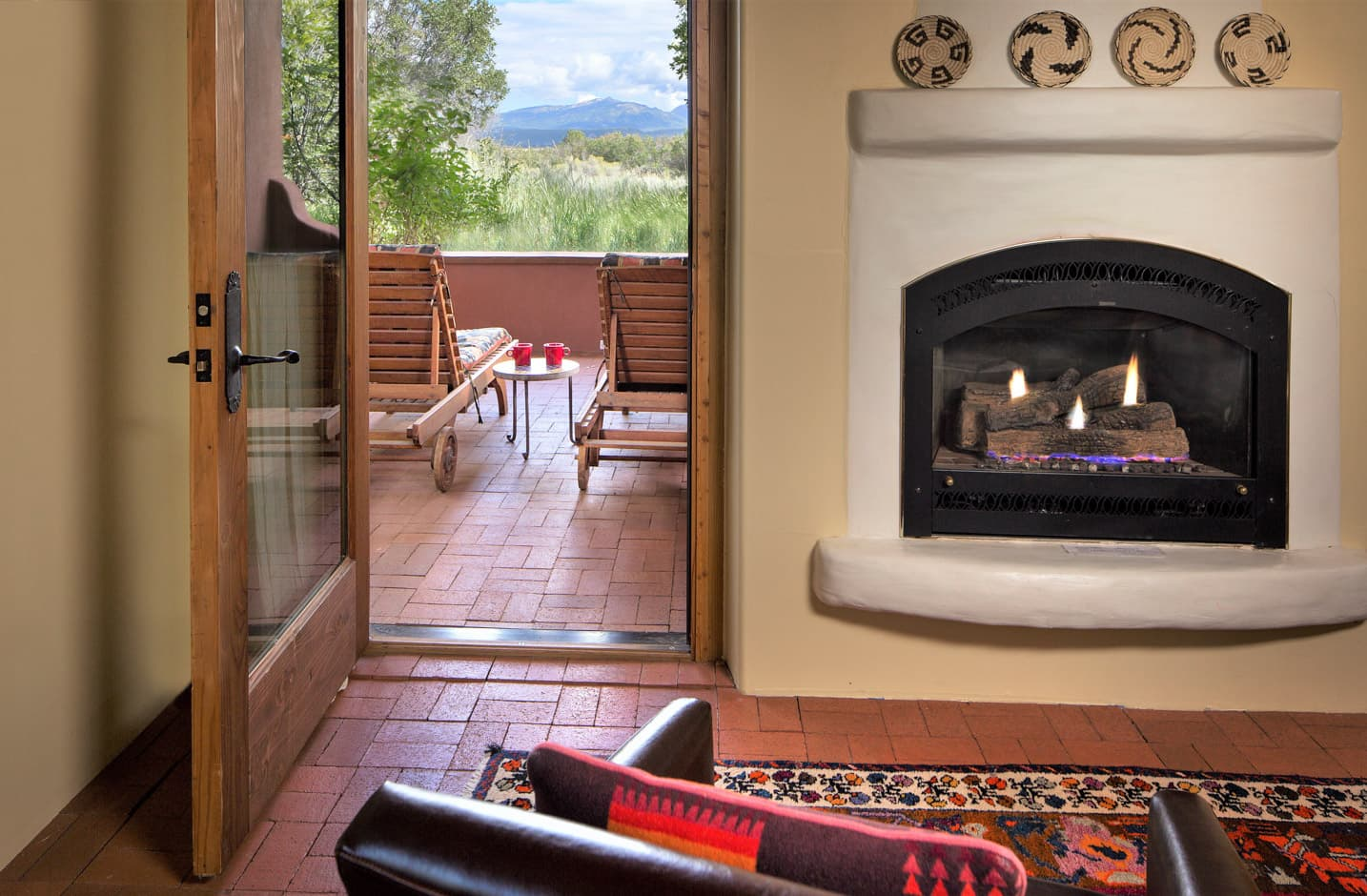 A gas firplace and a patio with two chairs and a view of a mountain