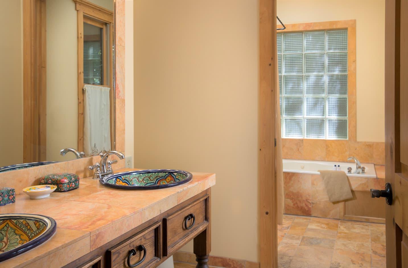 Whirlpool tub in a bathroom with ornate vanity sinks