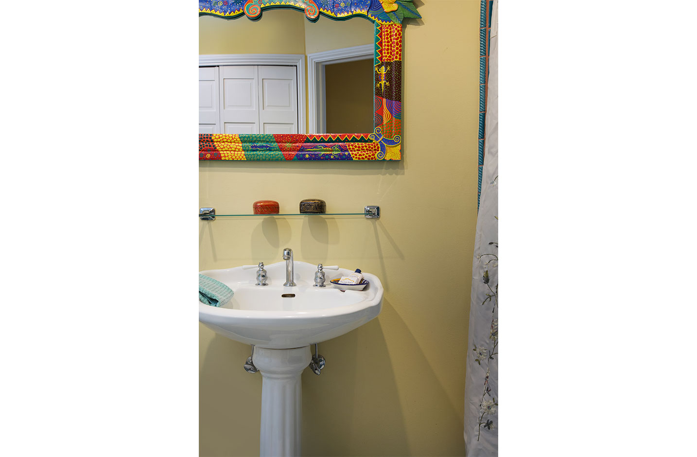 Bathroom sink with a colorful framed mirror