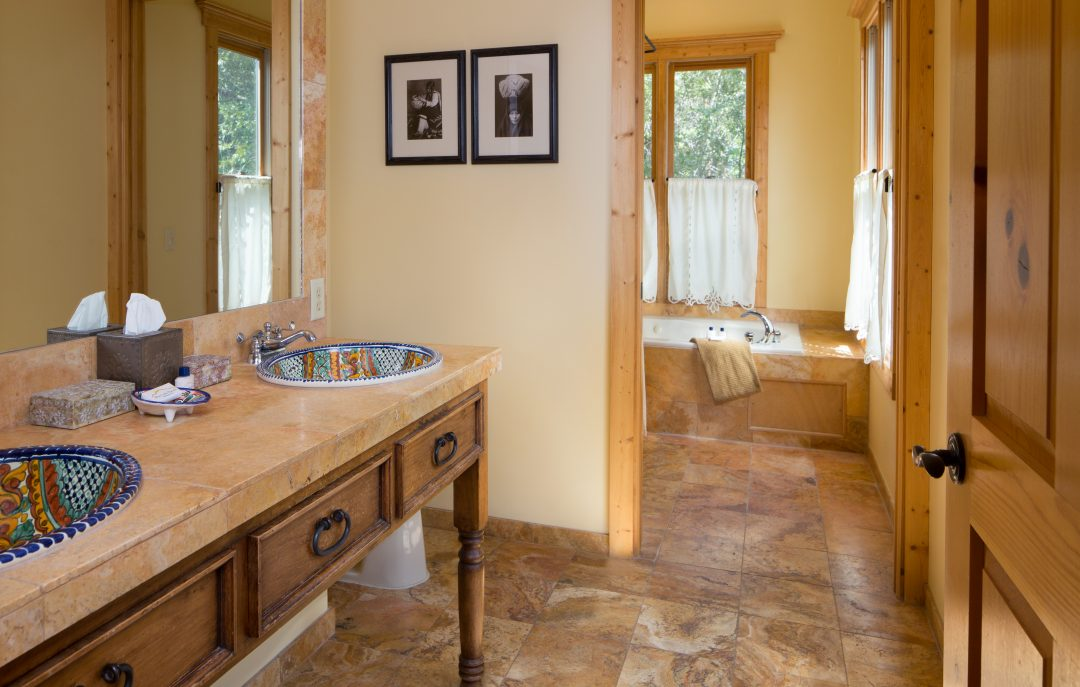 Spacious bathroom with sinks and Whirlpool tub and ample natural light
