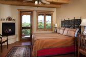 Bedroom with a king bed, fireplace, and ceiling fan, a door leads to outside patio