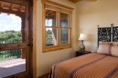 King bed and door to outside patio with sweeping views