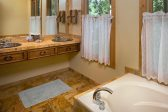 Bathroom with Whirlpool tub, sinks, and windows