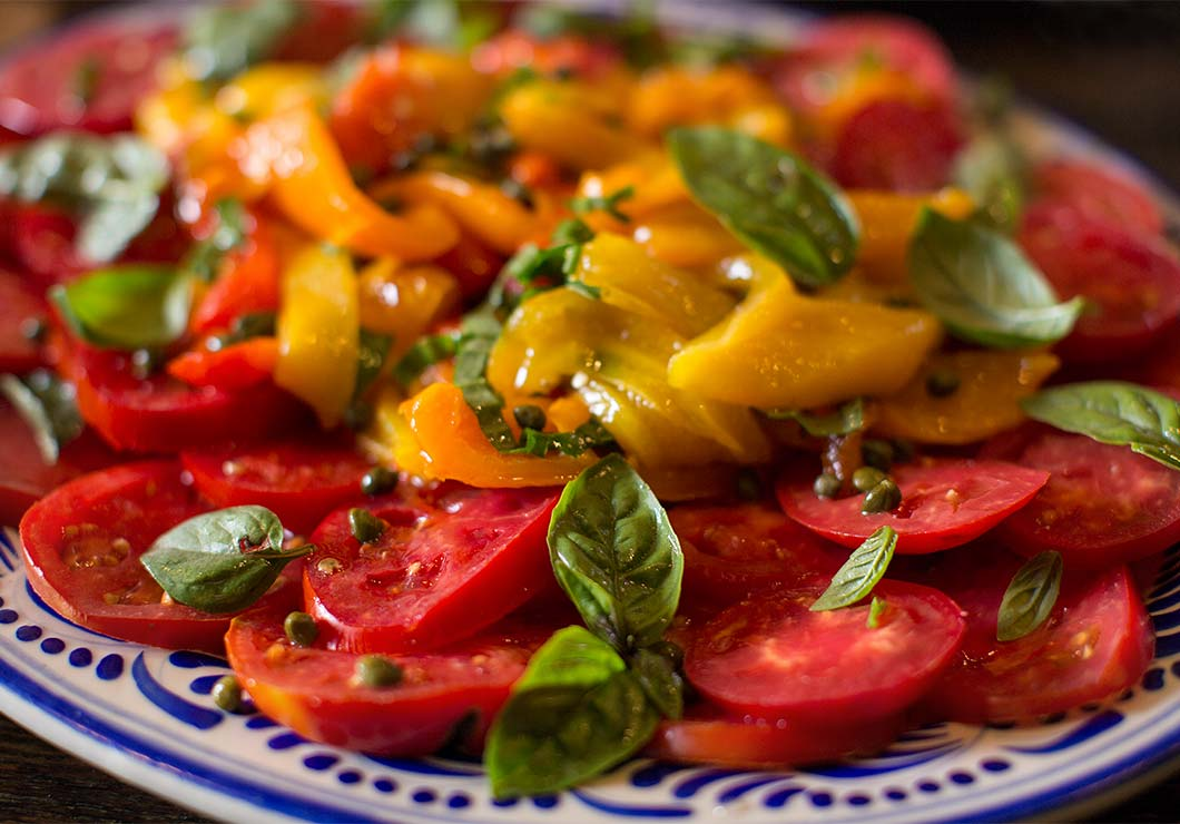 Sliced tomatoes, orange and yellow bell peppers and basil on a plate