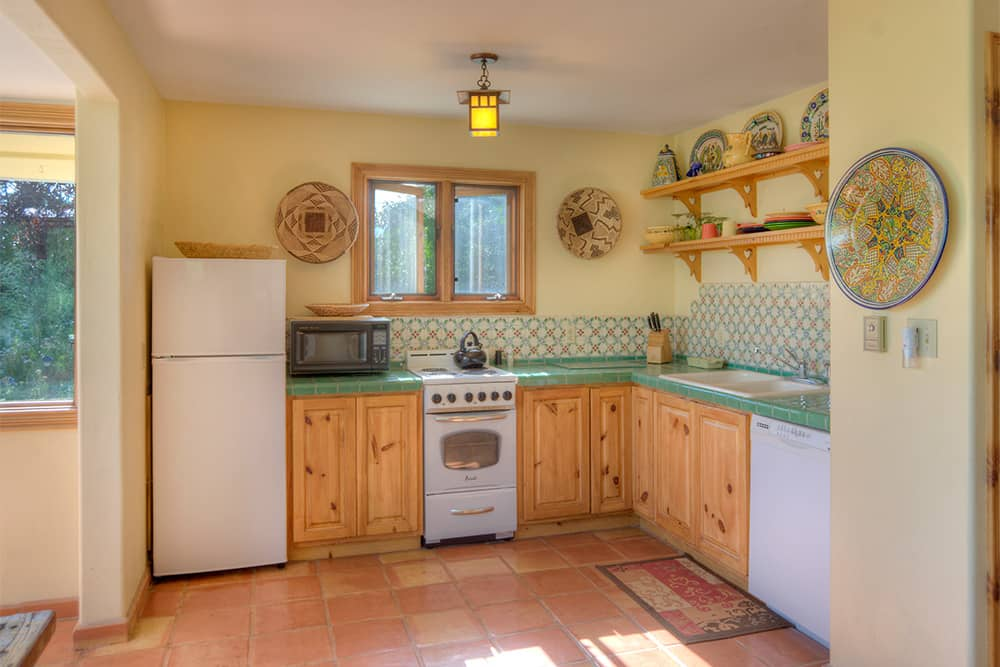 A kitchen with a stove, microwave, fridge, tile floors and counters