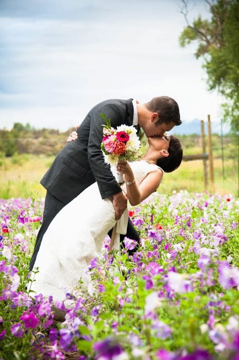bride and groom kiss while standing in a bed of flowers