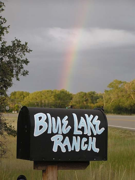 A mailbox with Blue Lake Ranch painted on it and a rainbow in the background