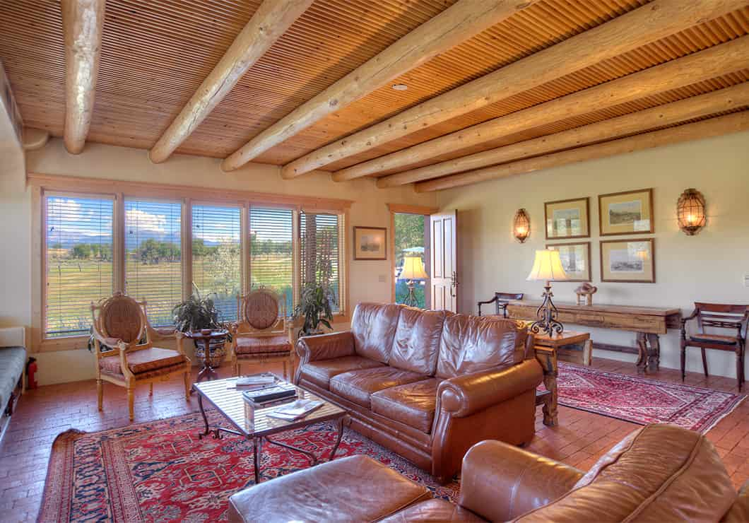 A large living room with leather couches and a view of the mountains