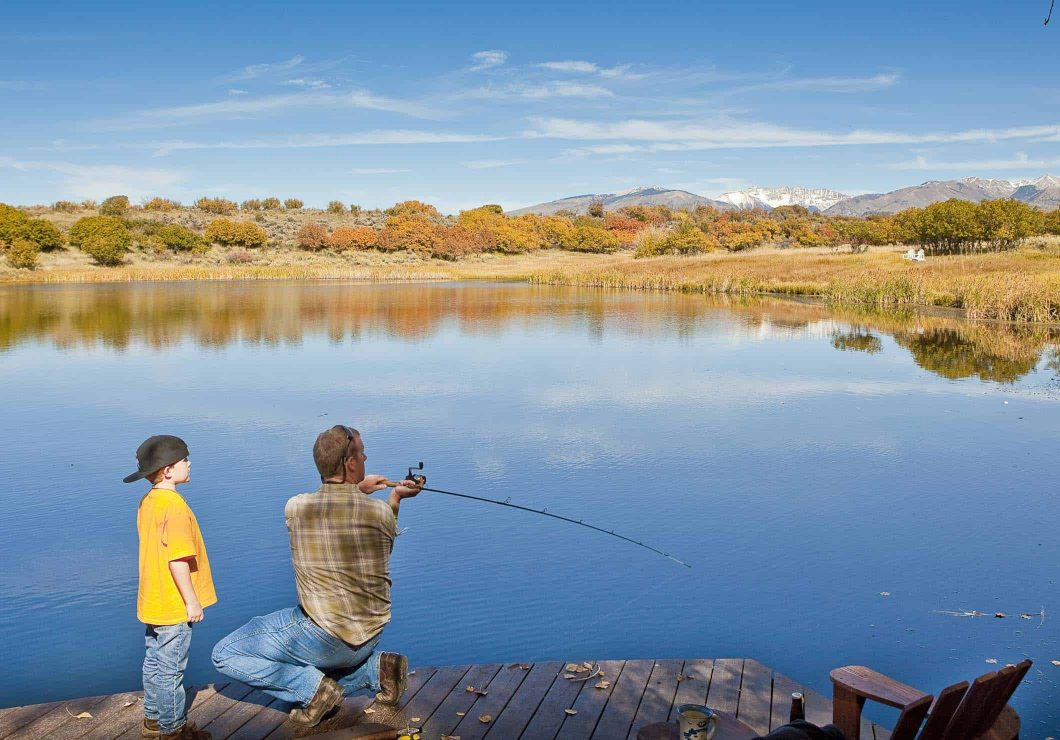 Father and Son fishing off the deck at the cabin on the lake at blue lake ranch